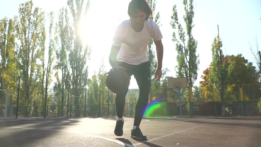 Young man is playing basketball outdoor #1019336194