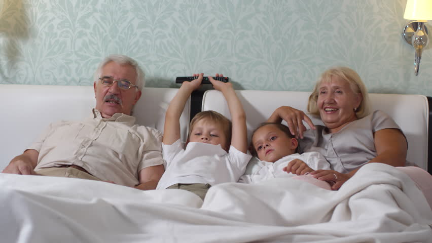 Cute little boy and girl lying on cozy bed between grandmother and grandfather while watching TV together at home | Shutterstock HD Video #1019360974