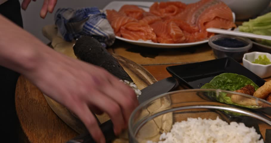 On wooden board lying sushi roll for cutting. Woman is preparing japanese food at home. | Shutterstock HD Video #1019363134