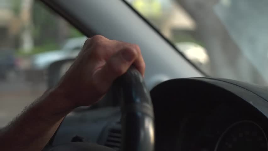 Close up of a man's hand on steering wheel - driving thru the city | Shutterstock HD Video #1019373934