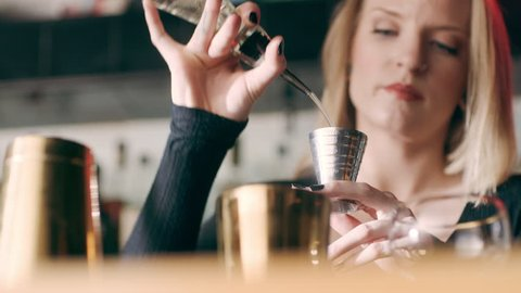 Skillful female bartender pouring shots of alcohol into a cocktail shaker in a fancy bar with soft interior lighting. Close up shot on 4k RED camera.
