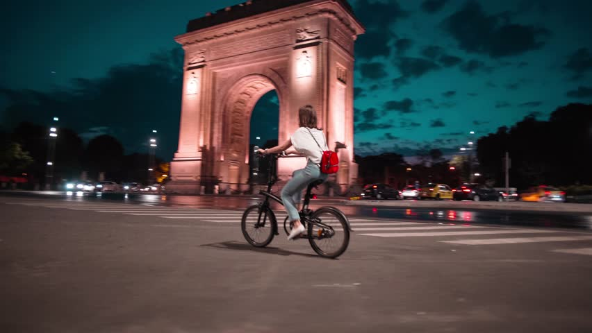 Tracking shot young woman biking riding a bike in front of Arch of Triumph Bucharest at dusk sunset