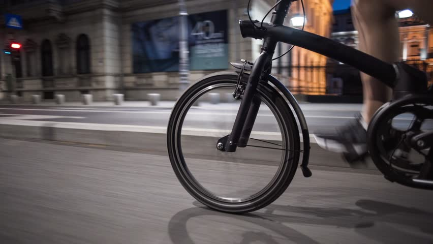 Tracking shot young man biking riding a bike on a city street lights at night in Bucharest    Shutterstock HD Video #1019496184
