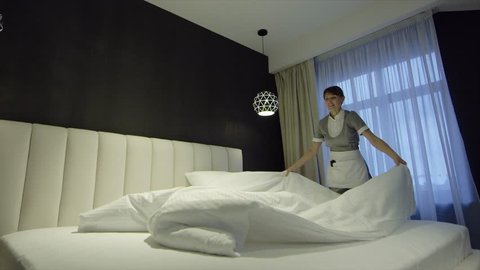 Chambermaid Makes Bed In Hotel Bedroom