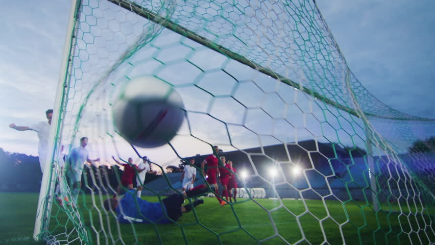 On Soccer Championship Player Kicks the Ball and Goalkeeper Tries to Defend Goals but Jumps and Fails to Catch the Ball. Camera Shot from Behind the Net with whole Stadium Visible. #1019537884