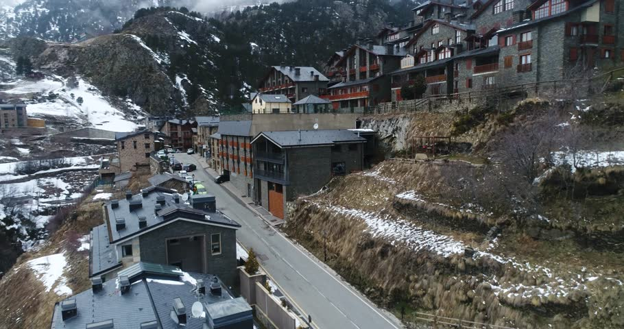 4k. Travel, drone view. Andorra. Europe. France. Fly over the mountains covered with snow. Sun shines over the summeries and blue sky. Little town between the mountains. Modern architecture #1019546014