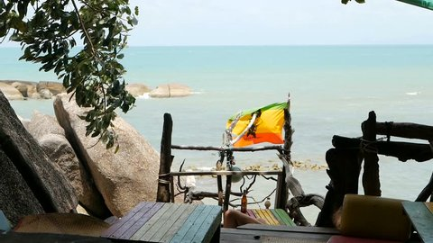 Relaxing jamaican cannabis rasta marijuana reggae bar on the tropical summer beach from wooden branches and thatch. Rastafarian flags with yellow, red and green colors and bob marley.