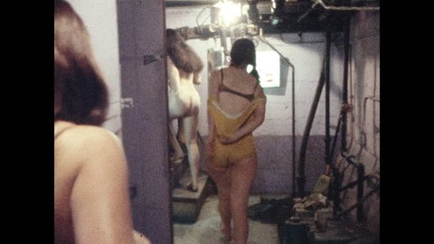 1970s: Burlesque performers pass through backstage basement area; woman in mini skirt walks across stage, speaking into microphone.