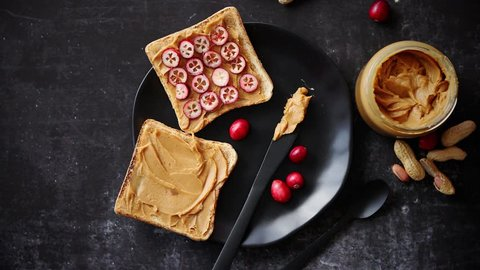 Toasts bread with homemade peanut butter served with fresh slices of cranberries. With jam jars and peanuts on side. Top view with copy space