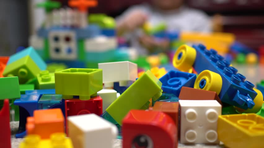 Little child playing with lots of colorful plastic toys indoor.    Shutterstock HD Video #1019639284