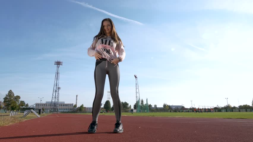 Fit sporty girl training outside on the tracks on a sunny morning. | Shutterstock HD Video #1019641624