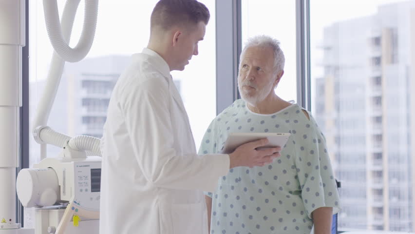 Handheld shot of male doctor explaining to patient over tablet computer in hospital ward