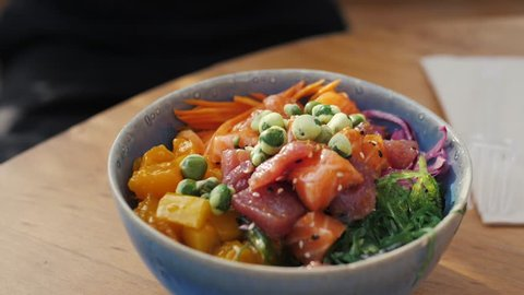 Raw Organic Ahi Tuna Poke Bowl with Rice and Veggies close-up on the table. Top view from above