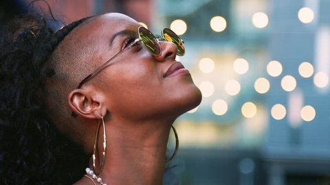 Young black woman looking up, turns to camera and takes off sunglasses, head shot, bokeh lights in background