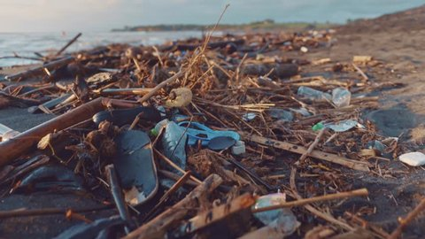 Plastic bottles, bags and other garbage dumped on dark sand of the beach and in ocean. Environmental pollution problem concept