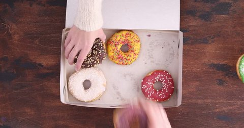 Top view of delicious sweet donuts. People take donuts out of the box on a wooden table background.