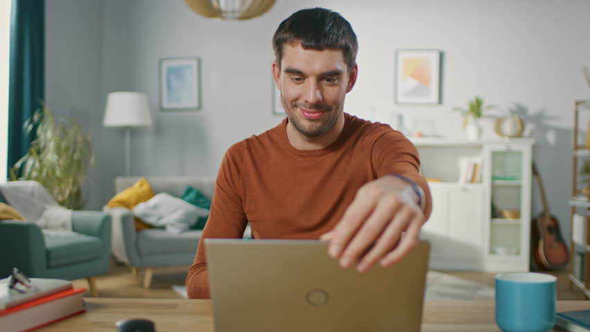 Confident Young Man Sitting at His Desk at Home, Opens and Starts Using Laptop. In the Background Living Room with Cozy Design. | Shutterstock HD Video #1019837074