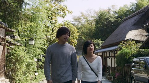 Millennial Japanese couple talking and walking past houses down a sidewalk in Kyoto, Japan with soft natural lighting. Medium shot on 4k RED camera.