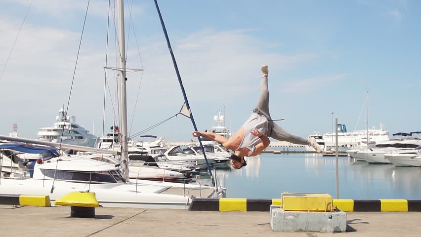 Muscular caucasian athlete increasing power with plyometric workout, doing extreme flip jumps at ocean pier or embankment, near seaside   Shutterstock HD Video #1019873104