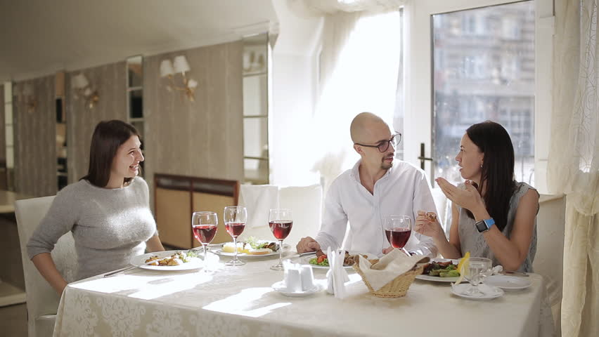 Meeting friends at the restaurant. Happy friends eating and drinking at restaurant.Four friends in the restaurant, eat meat and drink red wine in the glass. | Shutterstock HD Video #1019875174
