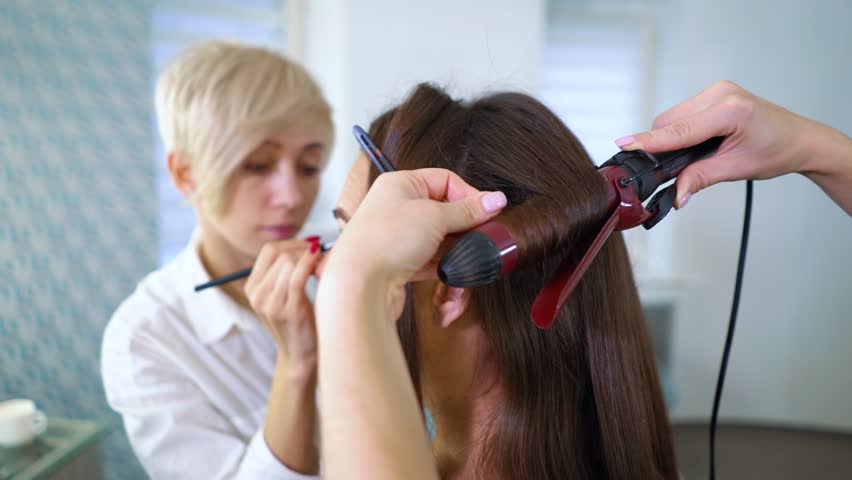 team of female makeup artists and hairdresser doing makeup and hairstyle to cute lovely young woman in beauty salon. people, cosmetics, care, lifestyle, style concept