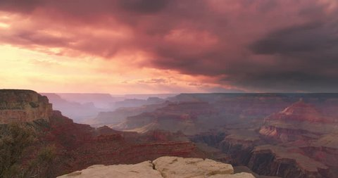Dramatic shot of Grand Canyon at sunset with amazing lighting, clouds, red cliffs and blue skies in 4K DCI. Camera pans right.