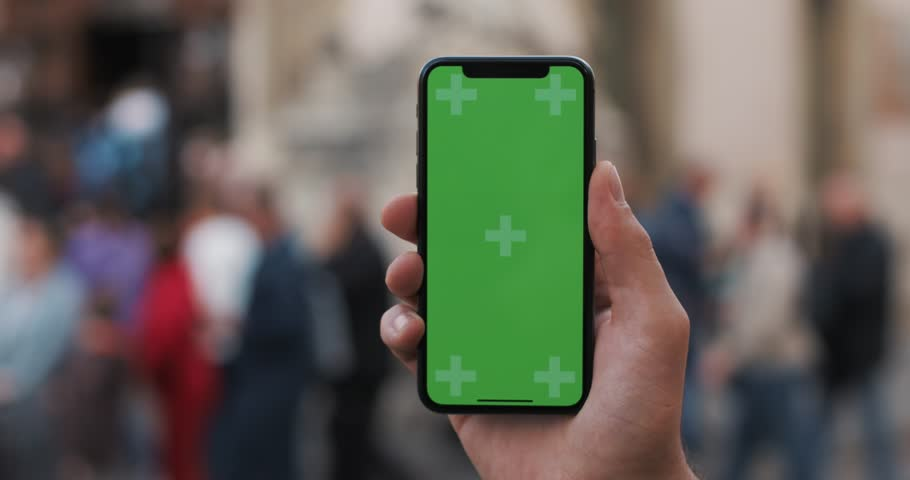 Closeup of a man's hand holding a mobile telephone with a vertical green screen on the streets #1019922544