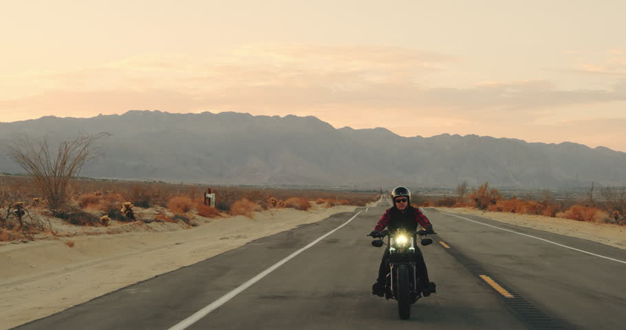 Happy man riding vintage black motorcycle down desert highway at sunset