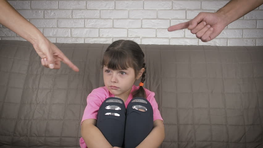 Child education. Parents scold daughter. Sad little girl on the couch, hands of parents scolding her. | Shutterstock HD Video #1019983654