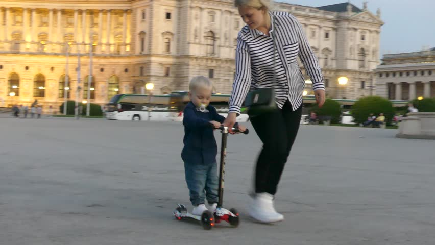 Vienna, Austria - May 11, 2018: A boy rides a scooter on Heldenplatz. A child on a scooter rides on Heroes' Square in Vienna. #1020054124