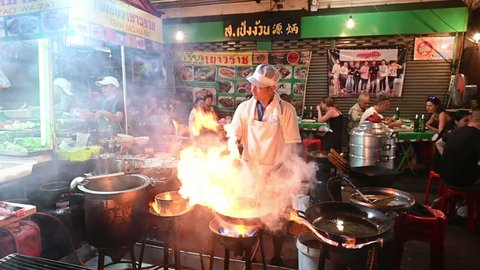 Bangkok, Thailand - November 24, 2018 : Slow motion a chef cooks food at a street-side restaurant in Chinatown