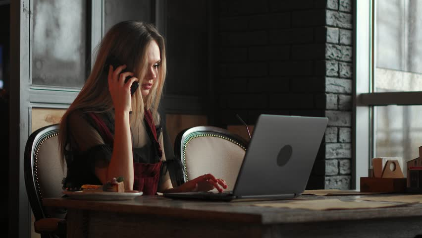 Young woman sitting in coffee shop at wooden table, drinking coffee and using smartphone.On table is laptop. Girl browsing internet, chatting, blogging. Female holding phone and looking on his screen. | Shutterstock HD Video #1020124654