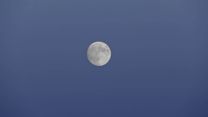 Full moon floating in clear blue sky at dusk