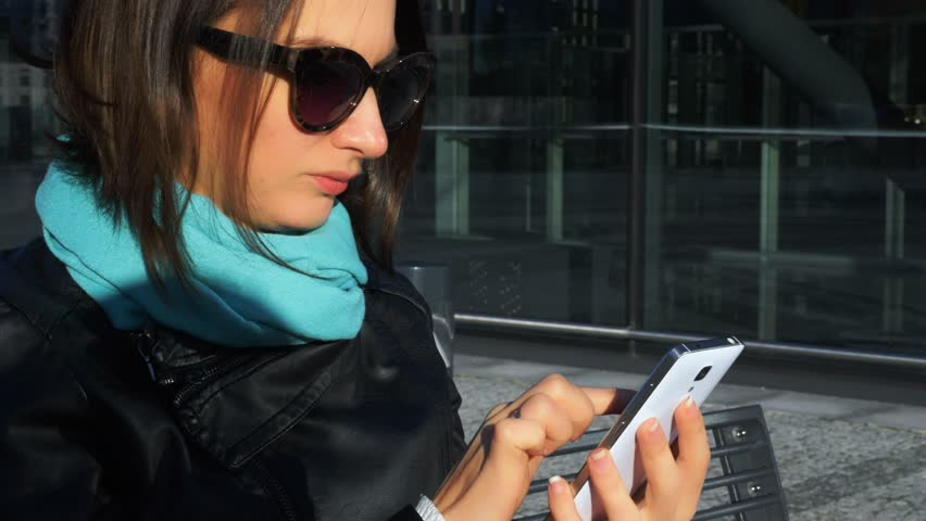 Young woman sits on bench outdoors and reads messages on her phone. One brunette girl communicates in social networks using her mobile on background of modern glass building, close up, stock video