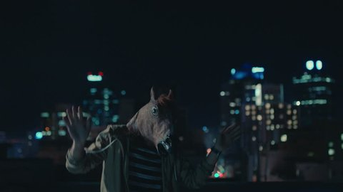 funny man wearing horse mask dancing on rooftop having fun performing silly dance moves celebrating weekend in urban city skyline
