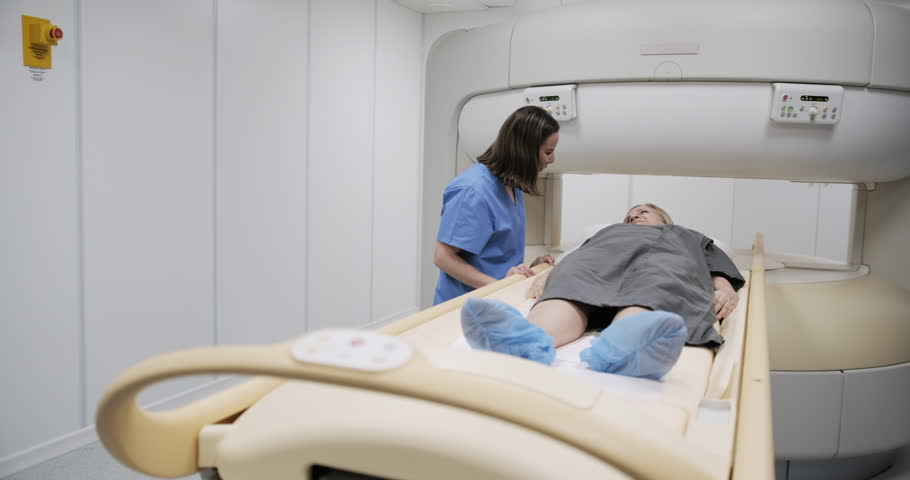 Senior sick patient and female nurse after MRI procedure in imaging lab inside hospital. Elderly woman talks with technician after medical therapy. People and disease prevention in health care. | Shutterstock HD Video #1020218134