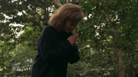 Thoughtful elderly asian woman clapping and bowing in front of a shrine in a beautiful green garden with soft natural lighting. Medium shot on 4k RED camera.