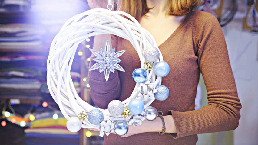Home made white braided Christmas wreath with decorations holding in hand HD. Camera dolly slide around a beautiful Christmas wreath with turquoise baubles on one side and star on middle.  | Shutterstock HD Video #1020269014