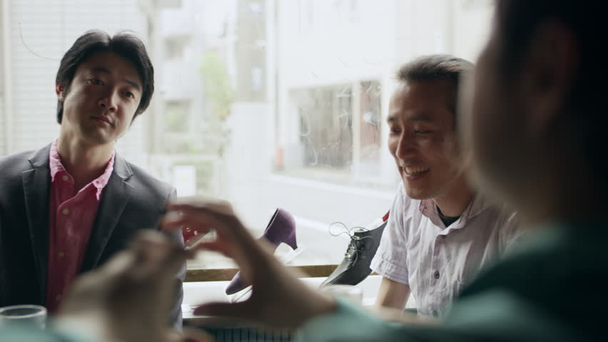 Group of Japanese friends sitting at a table with their drinks talking happily and having fun in a cool bar with soft natural lighting. Medium shot on 4k RED camera.