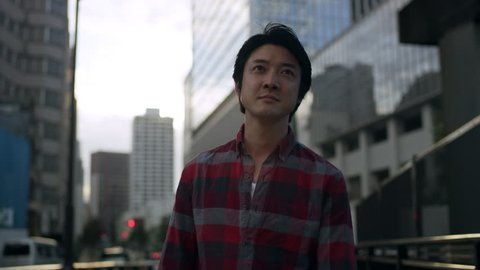 Casual Japanese man walking down a quiet city street and stops to answer his mobile phone with a look of concern with soft natural lighting. Medium shot on 4k RED camera.