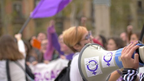 Barcelona, Spain. November 25th 2018: Megaphone Close Up with feminist stickers. Defocused women on the frame with arms up and jumping. Feminist Activists in a Demonstration. March