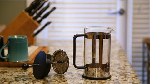Water being poured into a french press on a kitchen counter top with coffee brewing and multi colored coffee mugs.