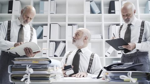 Businessman doing multiple tasks in the office at the same time: work efficiency and organization concept