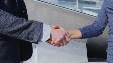 Handshake - business people shaking hands. Handshake between business man and business woman outdoors by business building. Casual wear, young people in their 30s. shaking hands close up. SLOW MOTION