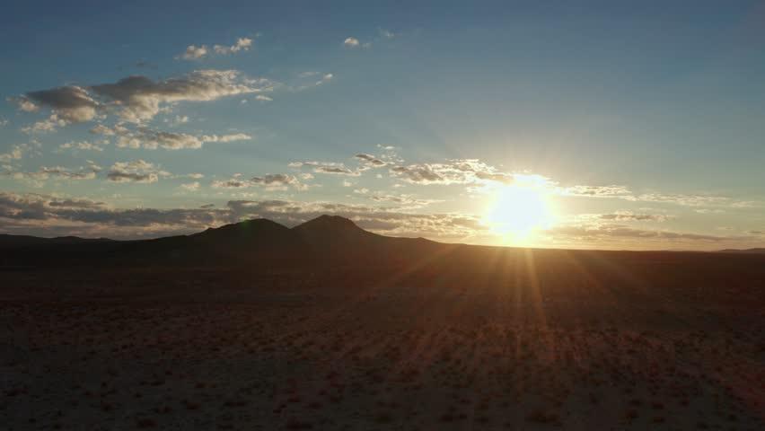 Bright starburst rising sun over Mojave Desert mountains and landscape, AERIAL #1020386824