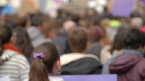Crowd of anonymous people in a March. Out of Focus women and men marching in a demonstration. A girl holds up a poster.