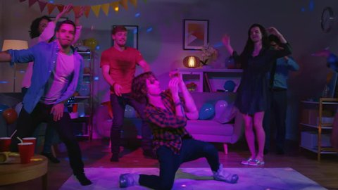 At the College House Party: Diverse Group of Friends Have Fun, Dancing and Socializing. One Guy Does Modern Dance Moves, Girls Cheer. Boys and Girls Dance in the Circle. Disco Neon Strobe Lights.