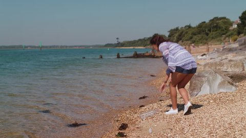 Young Woman Walks Along Beach and Picks Up Plastic Bottle