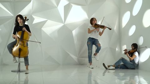 Two girls playing the violins one on the cello in the white studio