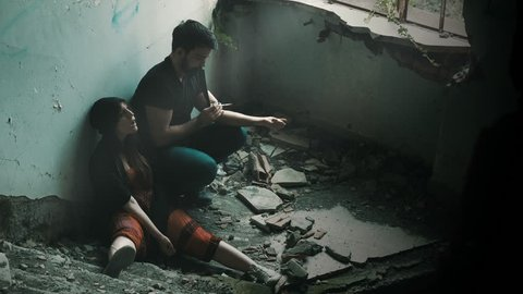 drug addicted people taking heroin in an abandoned building